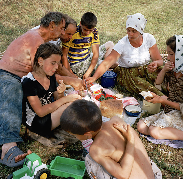 """Rena Effendi, The Borca family relaxes after a working day that started early. Gheorghe and Anuța Borca were married in July 1995, in the middle of the grass-cutting season. The honeymoon had to be shortened. """"We started making hay again one week after the wedding,"""" Anuța says ruefully. This photograph was made in Maramureș, the Romanian-speaking part of northern Transylvania, 2012. From the series: Transylvania: Built on Grass, 2012 © Rena Effendi, Prix Pictet"""